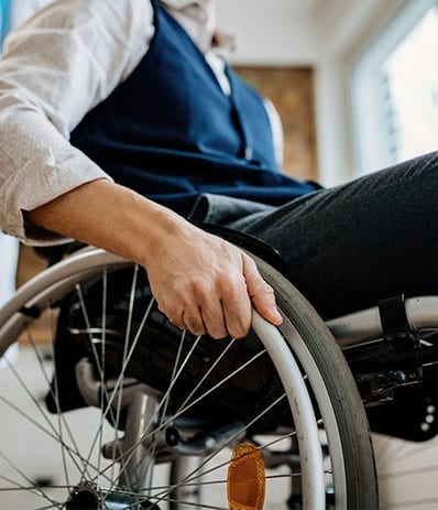 Close-up of disabled man in wheelchair and a nurse at home.