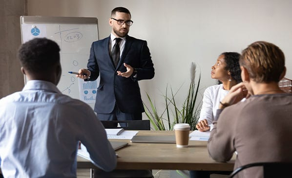 Confident businessman giving flip chart presentation at corporate meeting, pointing at diagrams on white board, business coach mentor explaining project strategy, employee presenting statistics