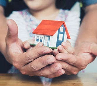 Hands holding small house after signing contract,concept for real estate,Insurance and safety concept with house protected by hands, moving home or renting property